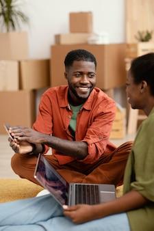 Smileypaar dat plannen maakt voor het renoveren van huis met behulp van laptop