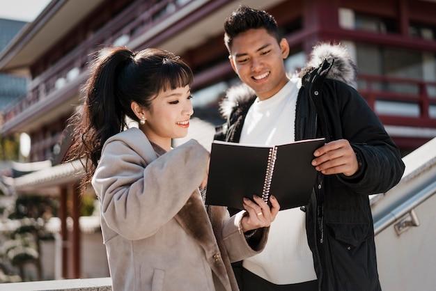 Smileypaar dat samen een notitieboekje bekijkt