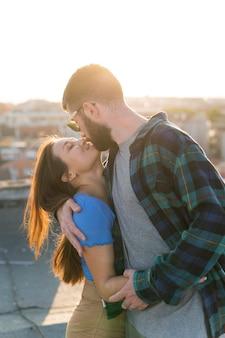 Smileypaar die elkaar buitenshuis kussen