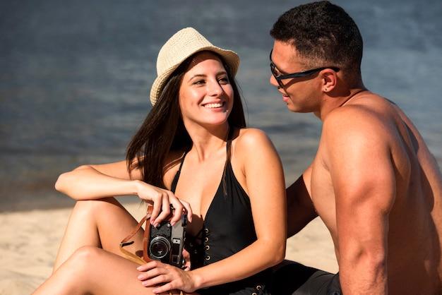 Smileypaar die van hun tijd op het strand genieten