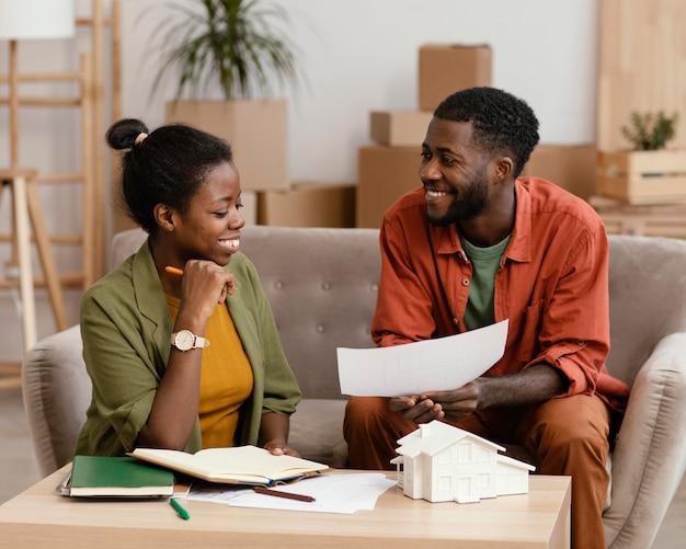 Smileypaar op de bank die plannen maken om huis samen opnieuw in te richten