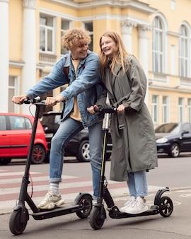 Smileypaar poseren samen buiten op elektrische scooters