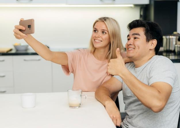 Smileypaar thuis tijdens de pandemie die een selfie met smartphone neemt