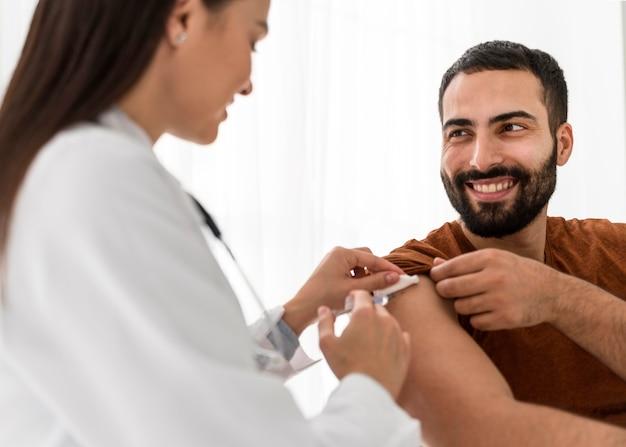 Smileypatiënt die de vrouwelijke arts bekijkt