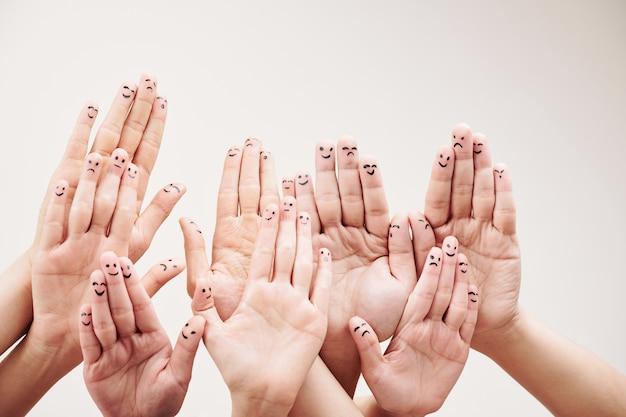 Smileys op vingers van mensenhanden