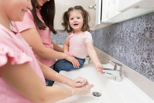 Smileysmeisjes die van de close-up handen wassen