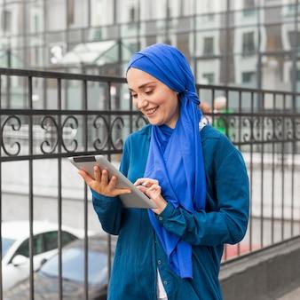 Smileytiener die op haar tablet kijkt