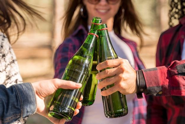 Smileyvrienden die met bierflesjes buitenshuis roosteren