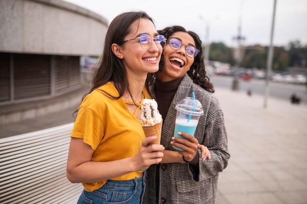 Smileyvrienden die samen buiten plezier hebben met milkshakes