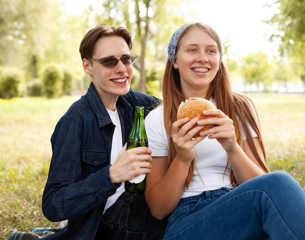 Smileyvrienden in het park met bier en hamburger