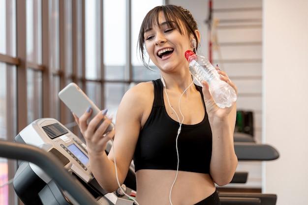 Smileyvrouw bij gymnastiek mobiel gebruiken