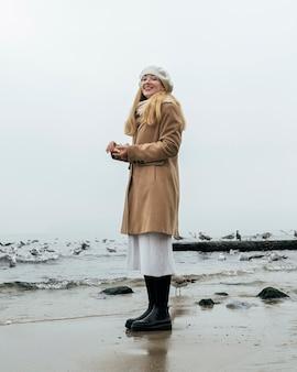 Smileyvrouw buiten op het strand in de winter