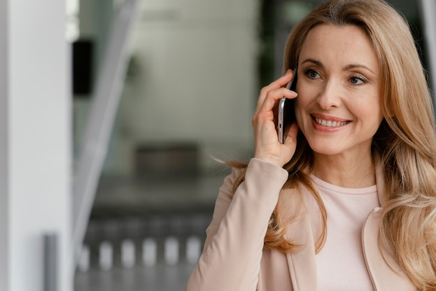 Smileyvrouw die aan de telefoon met exemplaarruimte spreekt