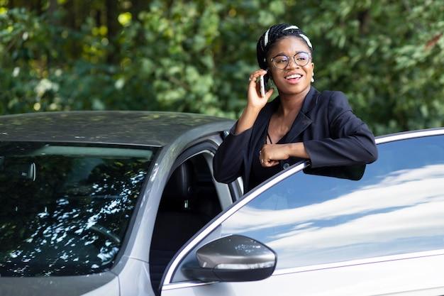 Smileyvrouw die aan de telefoon spreekt terwijl ze bijna in haar auto stapt