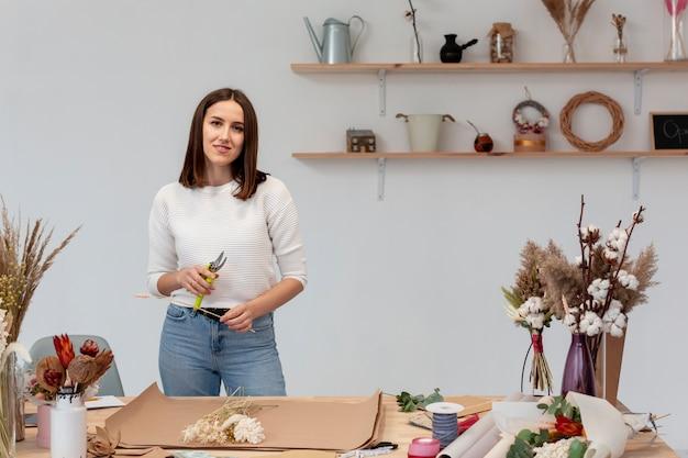 Smileyvrouw die aan een bloemenwinkel werken