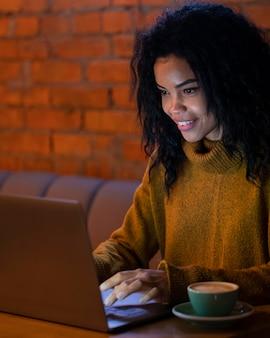 Smileyvrouw die aan haar laptop in een coffeeshop werkt