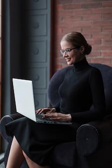 Smileyvrouw die aan laptop werkt