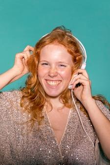 Smileyvrouw die aan muziek op haar hoofdtelefoons luistert