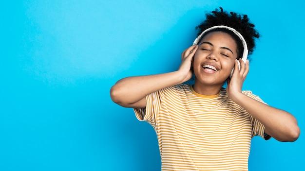 Smileyvrouw die aan muziek op hoofdtelefoons luisteren