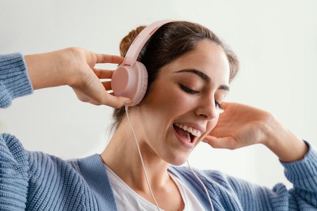 Smileyvrouw die aan muziek op hoofdtelefoons luistert