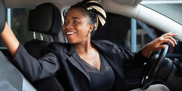 Smileyvrouw die achter haar auto wegkijkt