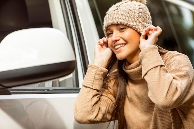 Smileyvrouw die beanie opzet tijdens een roadtrip