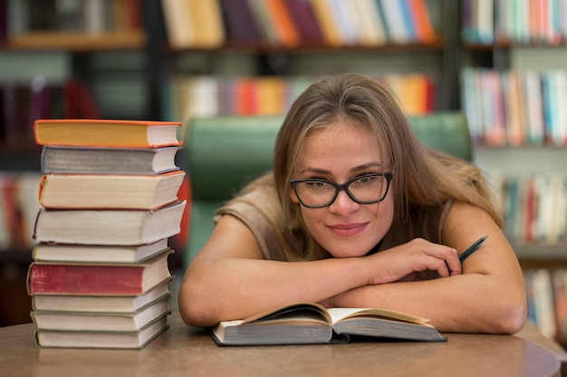 Smileyvrouw die bij bibliotheek bestudeert