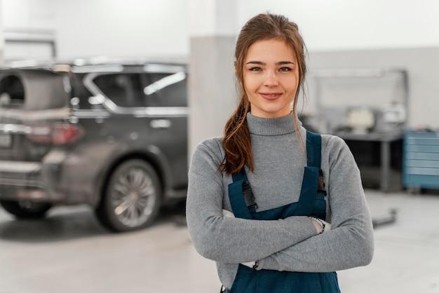 Smileyvrouw die bij een autodienst werkt