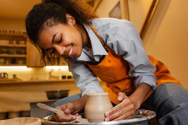 Smileyvrouw die binnenshuis aardewerk doet