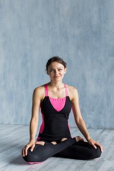 Smileyvrouw die de camera onderzoeken tijdens haar yogasessie