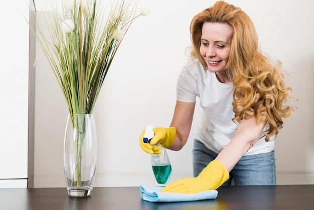 Smileyvrouw die de lijst schoonmaakt