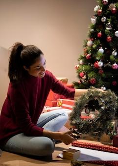 Smileyvrouw die decoratie voor christams maakt Gratis Foto