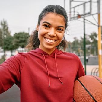Smileyvrouw die een basketbal houdt