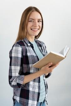 Smileyvrouw die een boek houden terwijl het bekijken camera