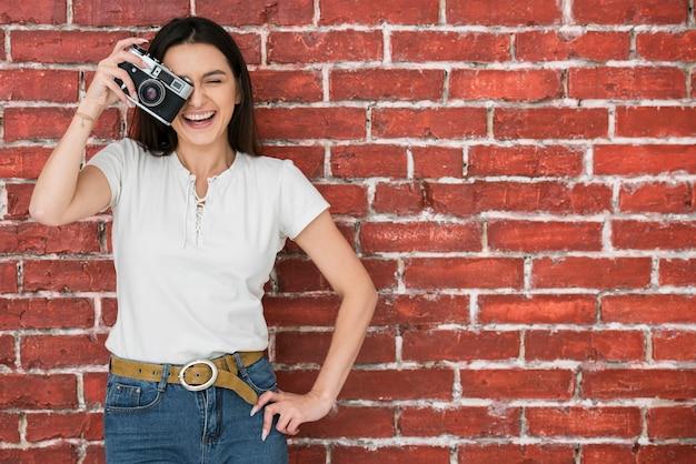 Smileyvrouw die een camera houdt
