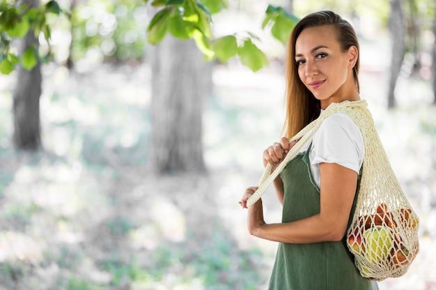 Smileyvrouw die een ecologische zak met exemplaarruimte houdt