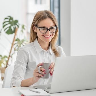 Smileyvrouw die een kop van koffie houden terwijl het hebben van een online conferentie