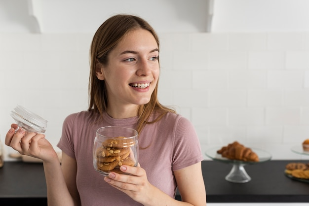 Smileyvrouw die een kruik met koekjes openen