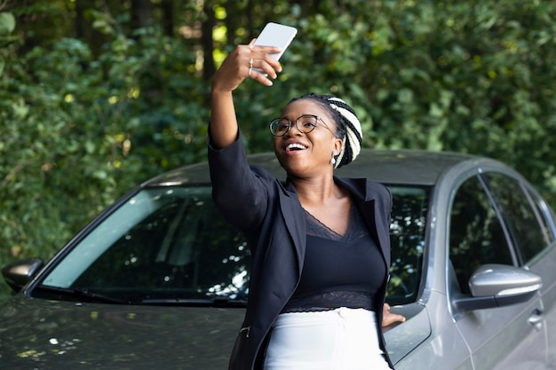 Smileyvrouw die een selfie met haar gloednieuwe auto neemt
