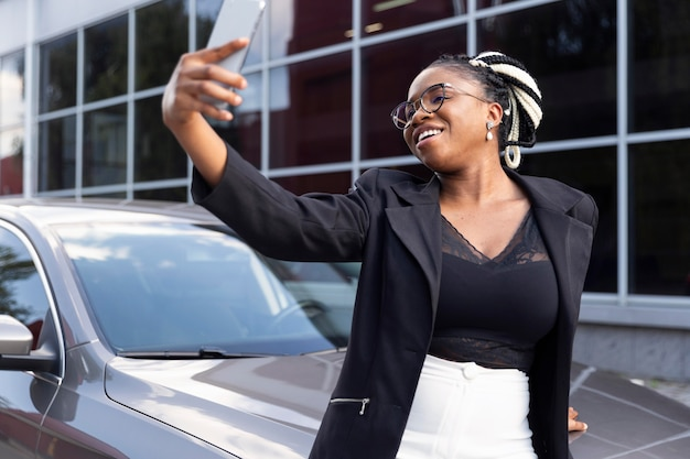 Smileyvrouw die een selfie met haar nieuwe auto neemt