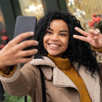 Smileyvrouw die een selfie met haar smartphone buitenshuis neemt