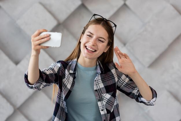 Smileyvrouw die een selfie met haar telefoon nemen