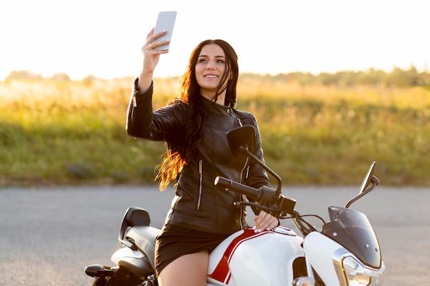 Smileyvrouw die een selfie neemt terwijl zij op haar motorfiets zit