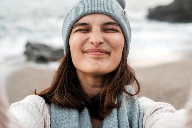 Smileyvrouw die een selfie op het strand neemt