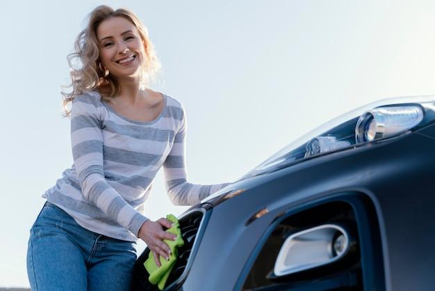 Smileyvrouw die haar auto buiten schoonmaken