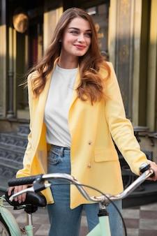 Smileyvrouw die haar fiets houdt en in de straat stelt