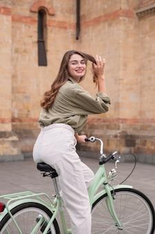 Smileyvrouw die haar fiets in de stad berijdt