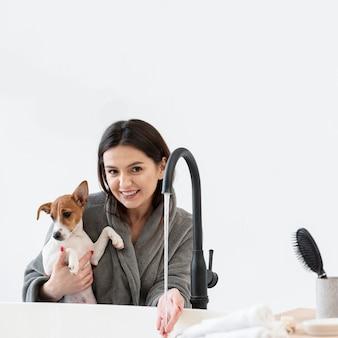 Smileyvrouw die haar hond houden terwijl het voorbereiden van een bad
