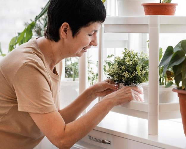Smileyvrouw die haar kamerplanten schikt
