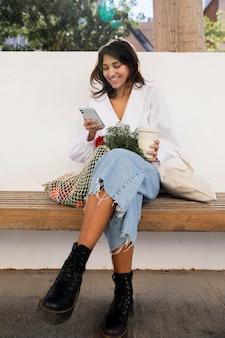 Smileyvrouw die haar smartphone buitenshuis gebruikt terwijl ze koffie drinkt